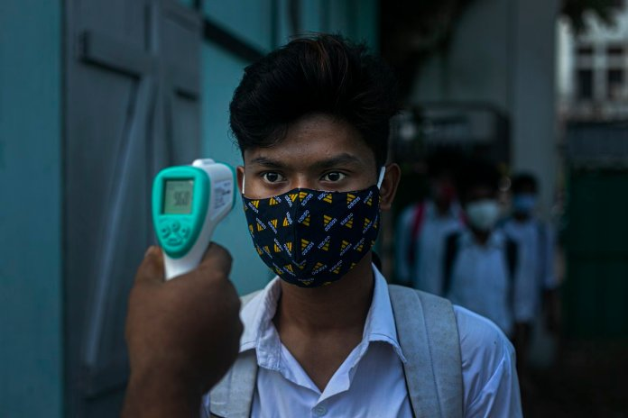 An employee checks the temperature of a student as schools reopen.(Representational image)