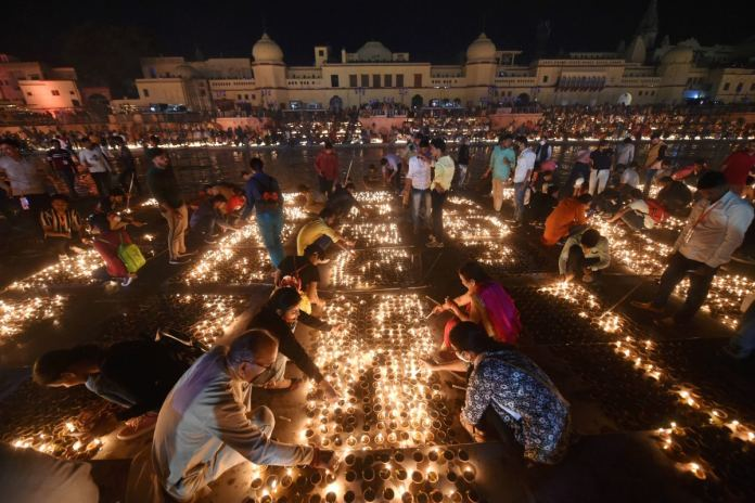 Devotees light earthen lamps on the bank of Saryu during Deepotsav celebrations in Ayodhya on Friday. (PTI)