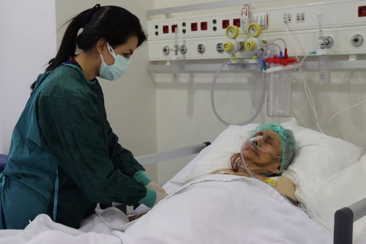 A nurse monitors Ayse Karatay at the City Hospital in Eskisehir, western Turkey, Saturday, Sept. 4, 2021. Karatay, a 116-year-old Turkish woman has survived COVID-19, her son said Saturday, making her one of the oldest patients to beat the disease. (AP)