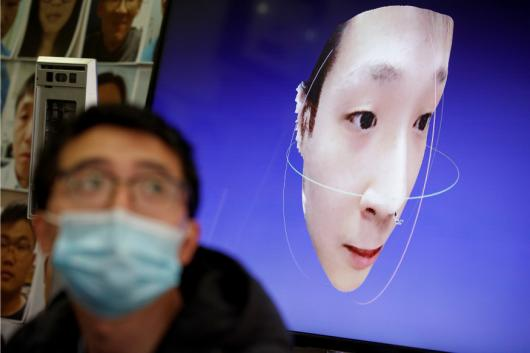A software engineer works on a facial recognition program that identifies people when they wear a face mask at the development lab of the Chinese electronics manufacturer Hanwang (Hanvon) Technology in Beijing as the country is hit by an outbreak of the novel coronavirus , China, March 6, 2020. Picture taken March 6, 2020. REUTERS/Thomas Peter