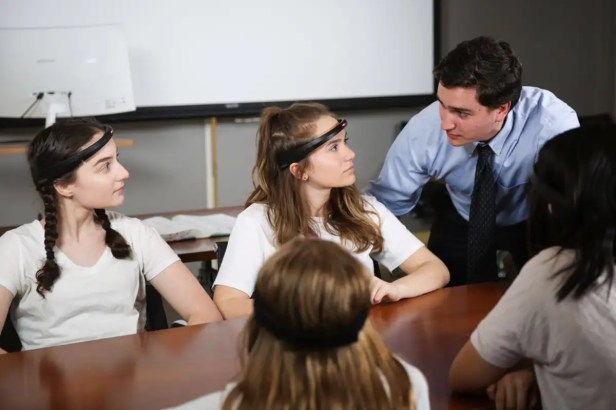 A person wearing the headset stares at their teacher