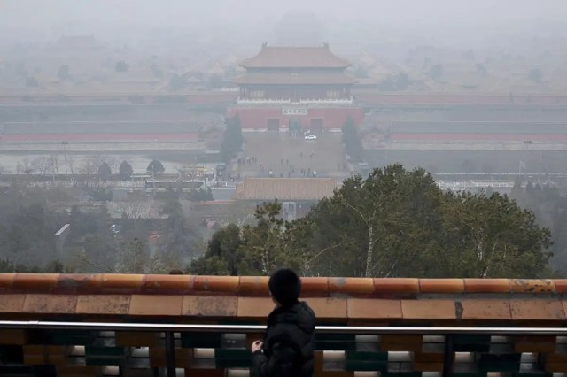 A man is looking at the north gate of the Forbidden City lost in the smog of pollution from the top of the Coal Hill, Beijing