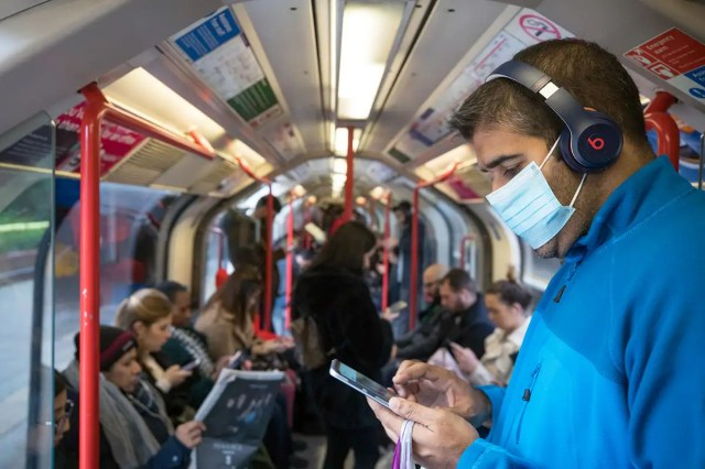 Man on train wearing mask and looking at his phone