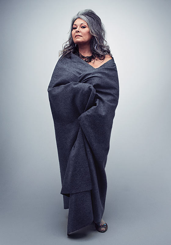 A gorgeous gray haired Roseanne stands wrapped in some kinda gray sheet.