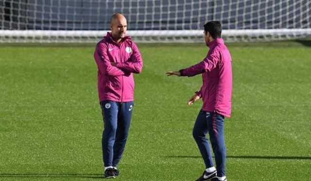 Manchester Citys Spanish manager Pep Guardiola (L) speaks with assistant coach Mikel Arteta during a team training session at the City Football Academy in Manchester, north west England on October 16, 2017, on the eve of their UEFA Champions League Group F match against Napoli. / AFP PHOTO / Paul ELLIS