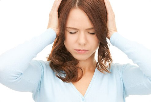 A woman attempts to silence her tinnitus by covering her ears.