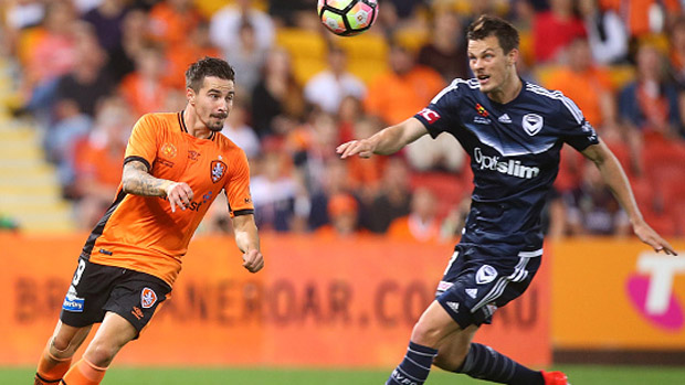 Victory defender James Donachie challenges for the ball with Roar striker Jamie Maclaren.