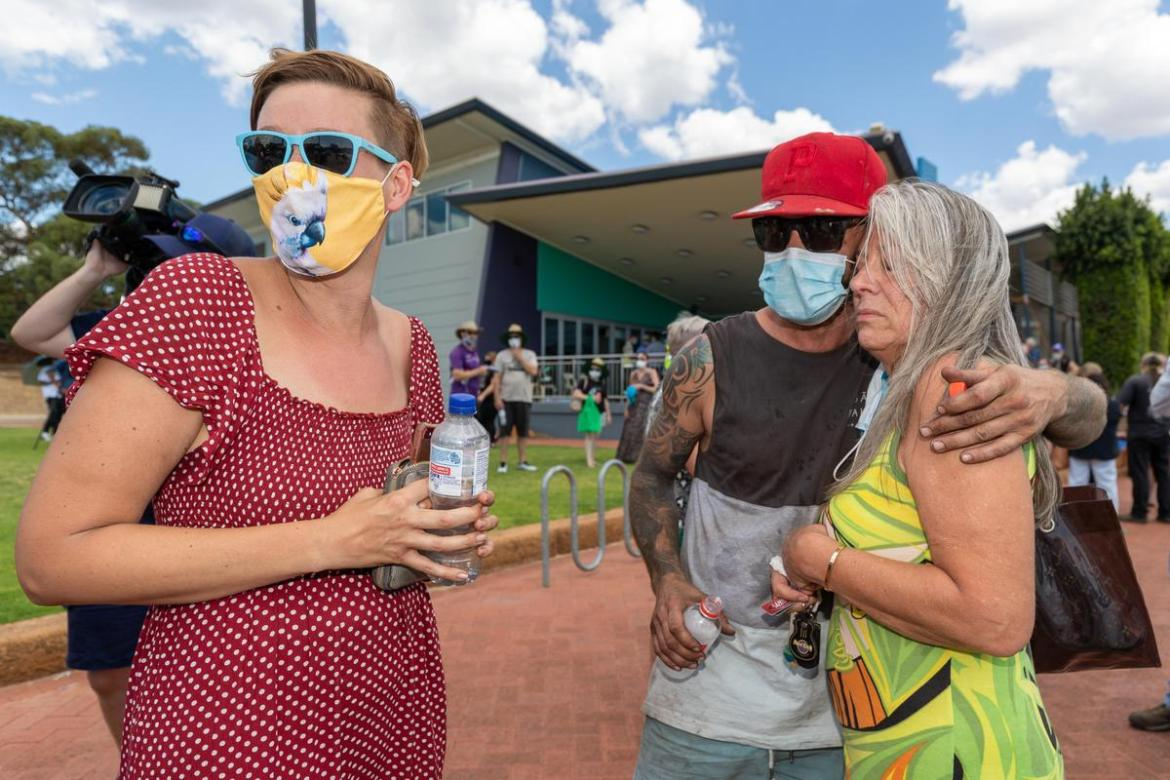 Pamela Wheeler-Hart (right) is comforted by neighbour Lee Lyons after talking to the media about her house that has been destroyed in Gidgegannup, Perth.