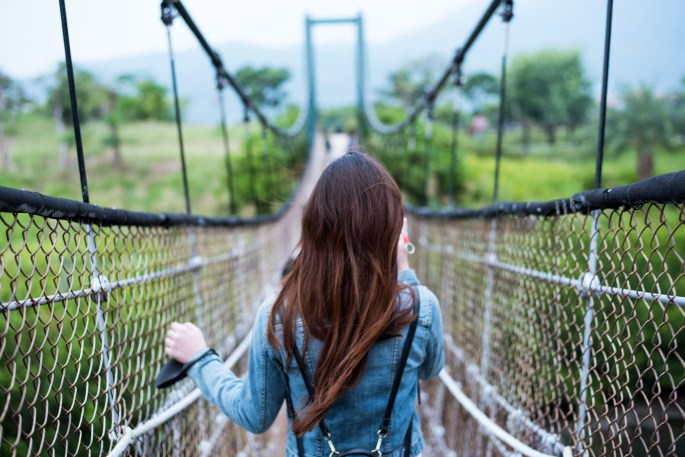Woman in Blue Long-sleeved Dress on Rope Bridge