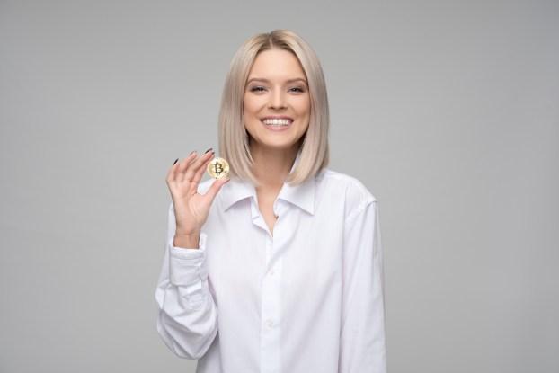 Women Wearing White Long-sleeved Collared Shirt Holding Bitcoin
