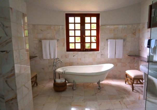 White Bathtub on White Tile Bathroom Near Brown Framed Clear Glass Window