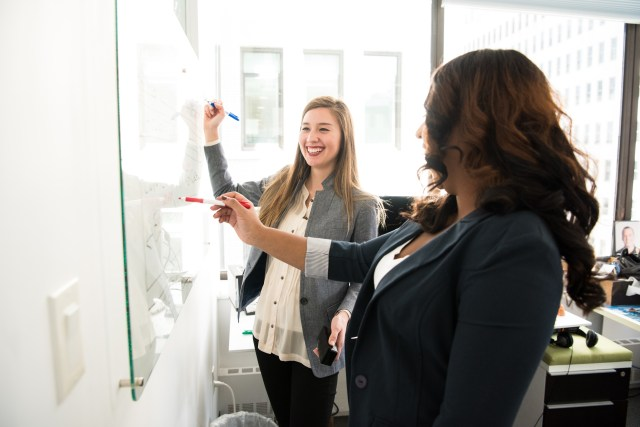 Two Women in Front of Dry-erase Board