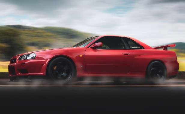 Selective Focus Photography of Red Nissan Gt-r R34 Skyline Running on Road
