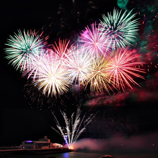 A pastel band of fireworks explodes in a dark sky, looking like a balloon bouquet