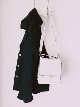 White Leather Crossbody Bag And Black Parka Coat