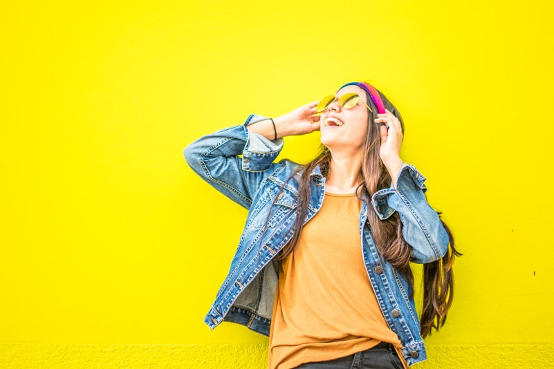 Smiling Woman Looking Upright Standing Against Yellow Wall