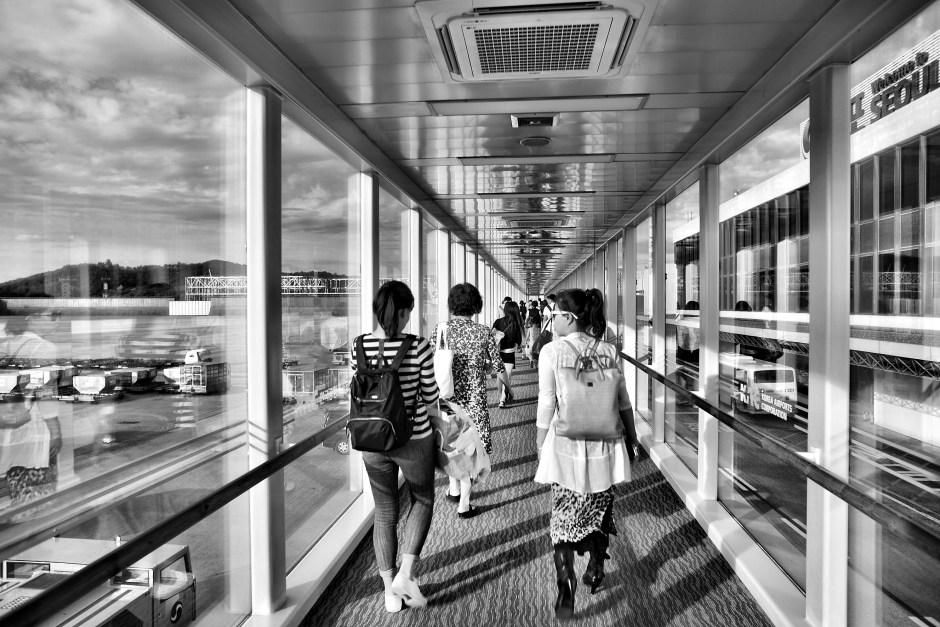 Foto em tons de cinza de mulher andando no caminho