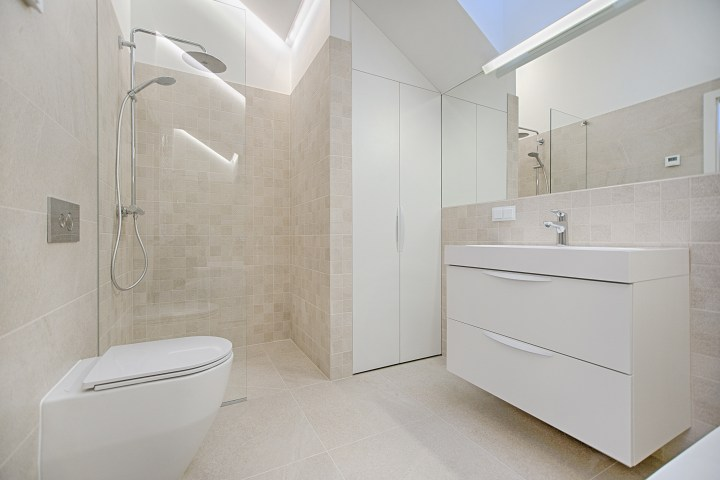 photograph of a bathroom with shower, toilet and sink unit