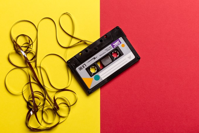 Black Cassette Tape on Top of Red and Yellow Surface