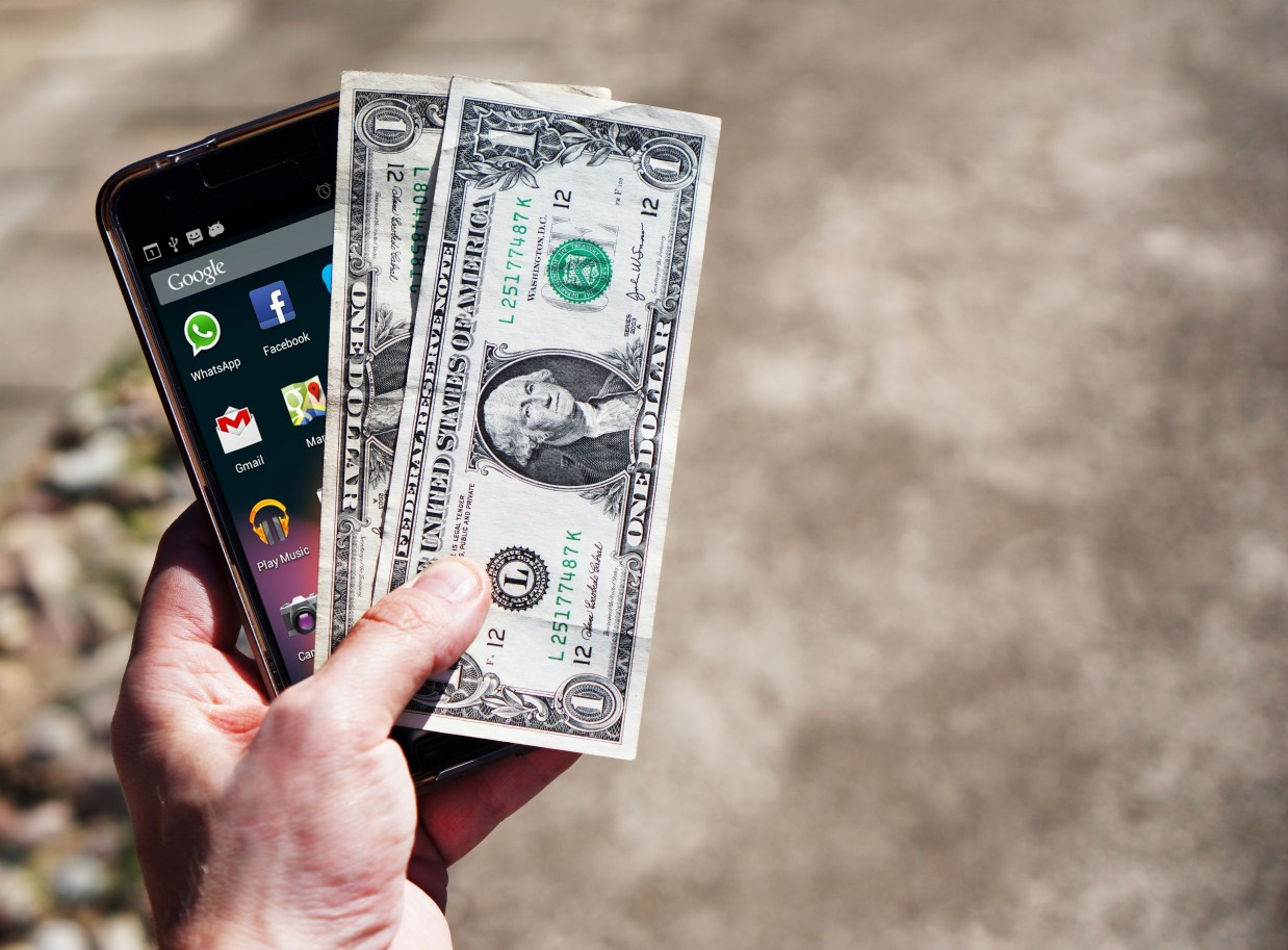 Persom Holding Black Android Smartphone and 2 1 U.s. Dollar