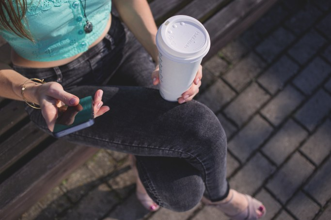 Woman Holding White Disposable Cup and Smartphone