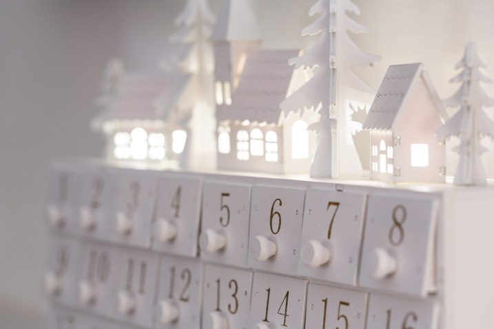 A white holiday themed custom advent calendar on a white surface.