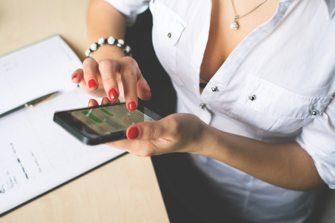 Woman in White Button Up Top and Holding Black Android Smartphone