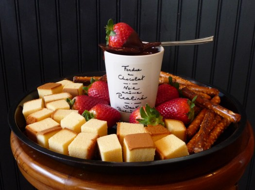 white ceramic mug on top sppon and strawberry surrounded leche plan and strawberry on black round shape tray