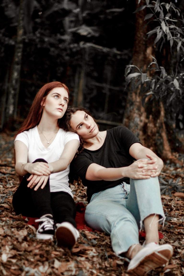 Two Women Sitting Near Trees