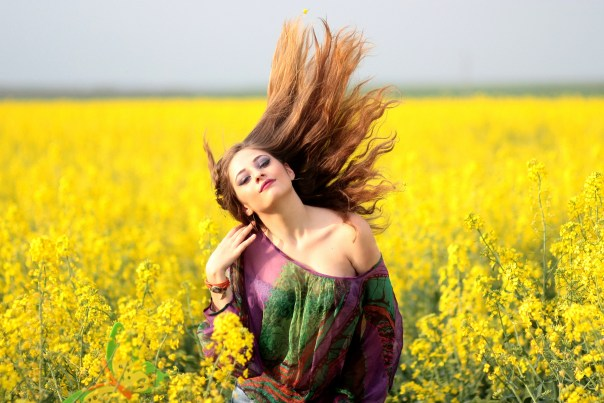 Portrait of Young Woman With Yellow Flowers in Field