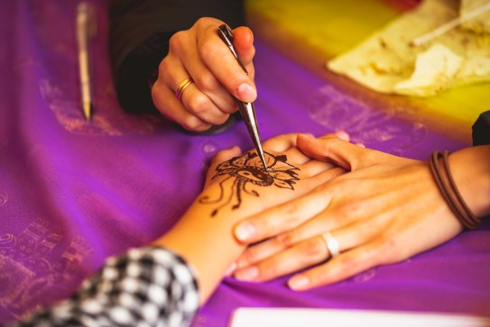 Close-Up Photo of Person Doing Mehndi Tattoo