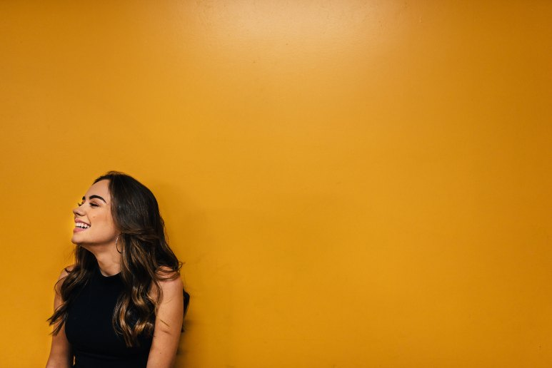 Photo of Woman Leaning Against Orange Wall