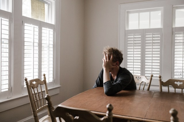 Photo of Man Leaning on Wooden Table