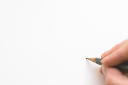 Primer plano de mano sosteniendo lápiz sobre fondo blanco
