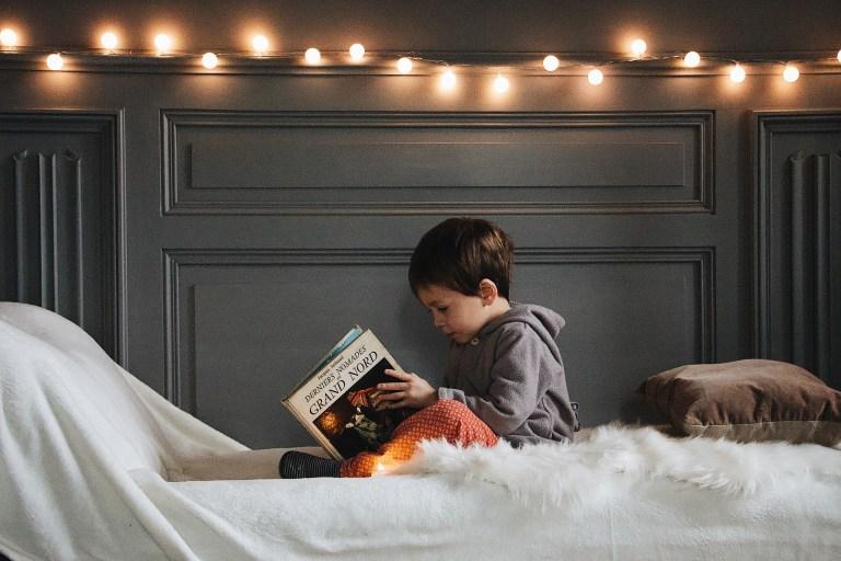 Boy in Gray Jacket Reading Book