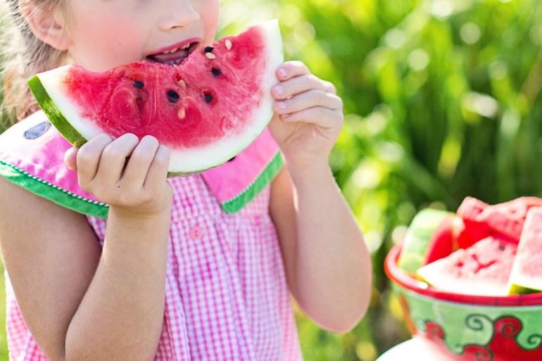 Girl Eating Sliced Watermelon Fruit Beside Table
