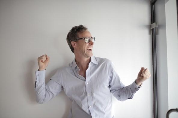 Portrait Photo of Laughing Man in White Dress Shirt and Black Framed Eyeglasses Celebrating