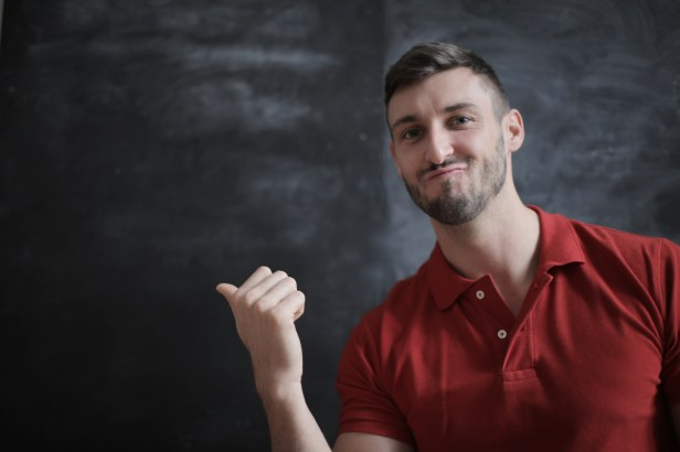 Man in Red Polo Shirt Standing Beside Chalk Board