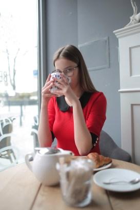 Donna In Camicia A Maniche Lunghe Rossa Che Beve Tè Verde