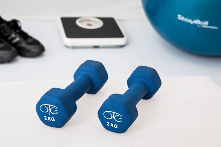 Two 2 Kg. Blue Hex Dumbbells on White Surface