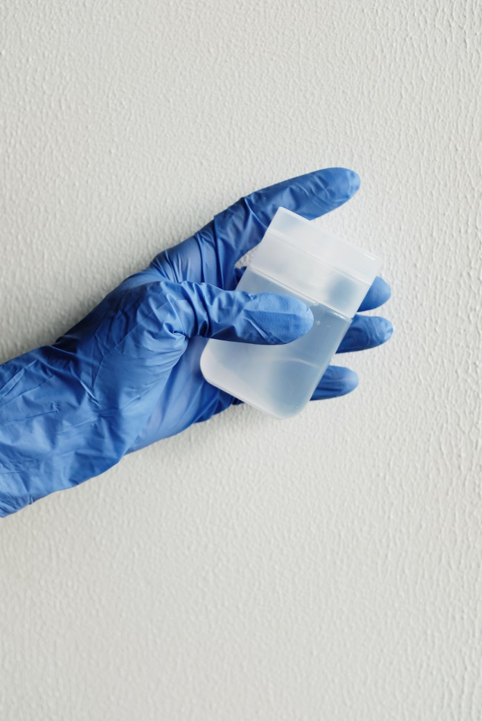 Person in Blue Gloves Holding White Plastic Bottle