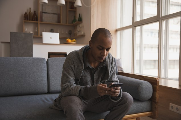 Focused young ethnic male messaging on smartphone at home