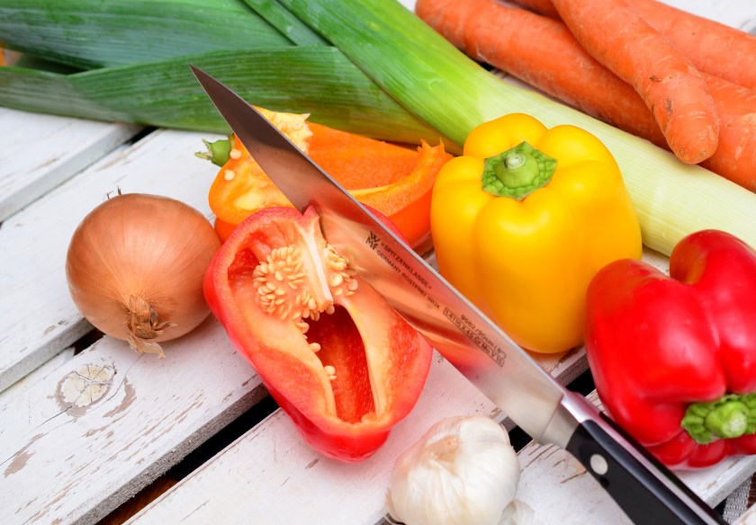 A kitchen knife cutting into vegetables.