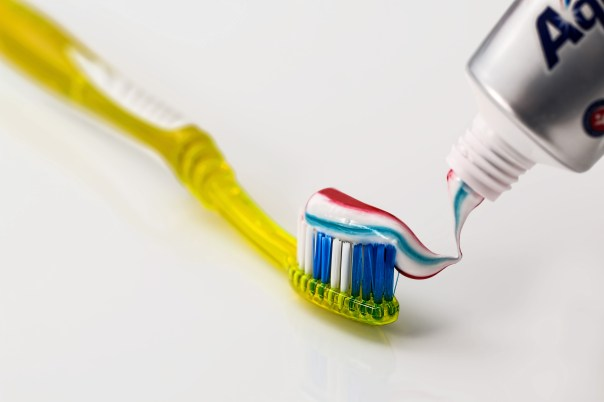 Toothpaste Being Put on Yellow Toothbrush