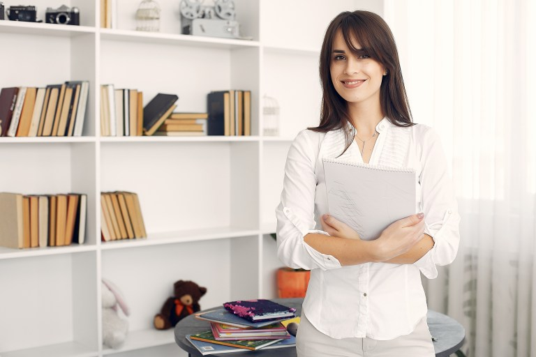 Cheerful young female home tutor with sketchpad in hands