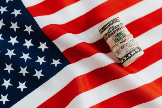 From above of United States currency folded in roll placed on USA flag illustrating concept of business profit and wealth