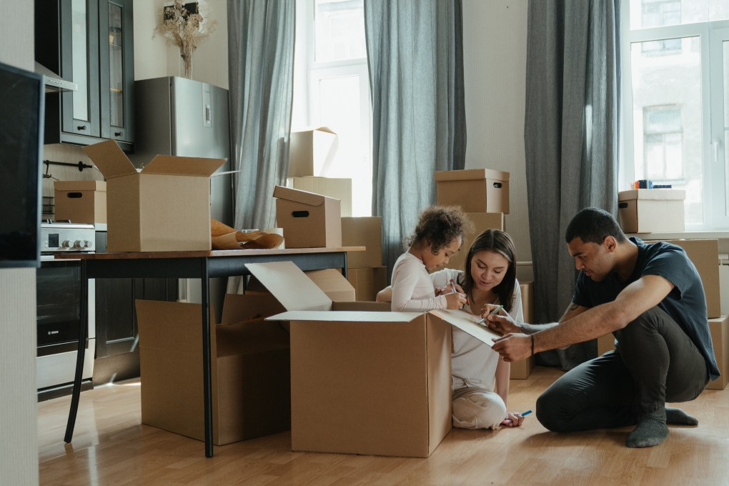 Family Unpacking After Moving (man, woman and girl)