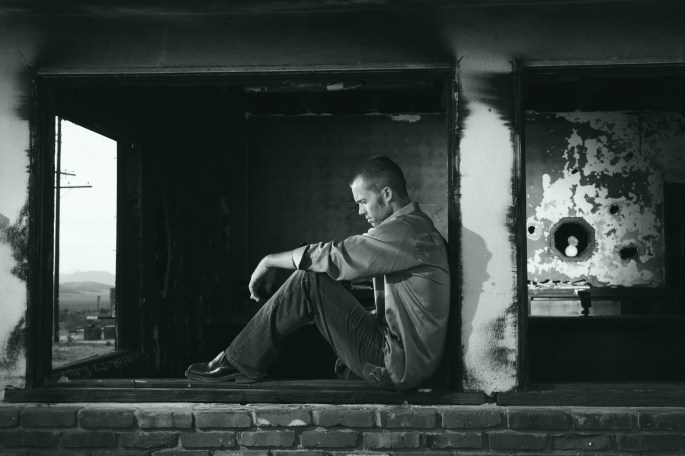 Grayscale Photo of Man Sitting