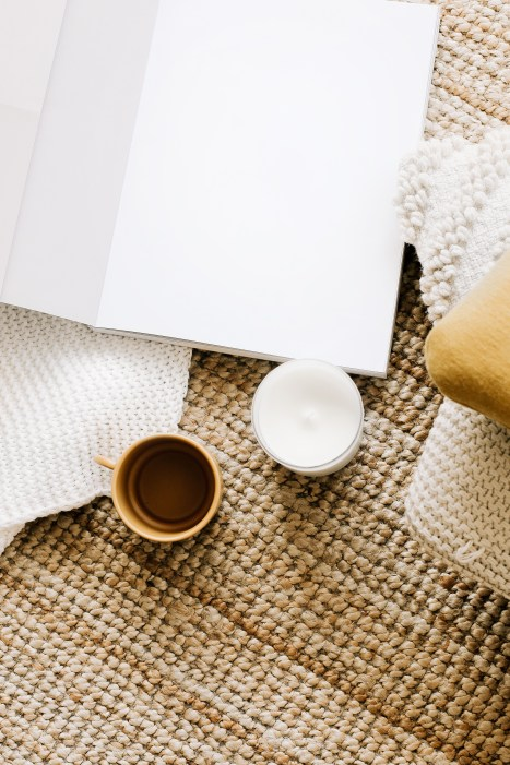 Top view arrangement of opened notebook with empty sheets placed on table near mug and candle