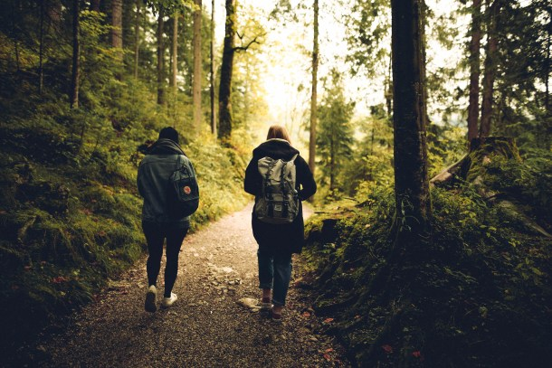 two girls walking a wooded path